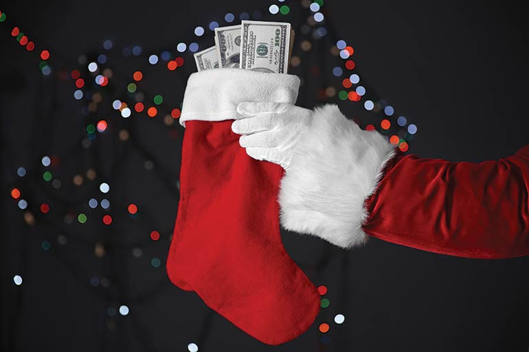 Santa holding a red stocking with money in it.